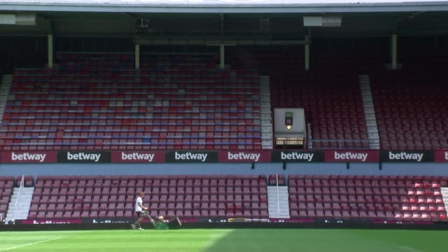 west ham last match at upton park: a look at the club's history; upton park: groundsman mowing the pitch zoom in to 'hammers' logo on seat covers... - グランドキーパー点の映像素材/bロール