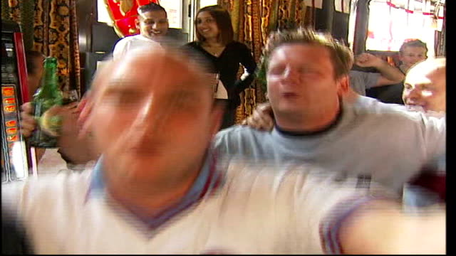 west ham united manager alan pardew sacked r01060510 int west ham fans celebrating in pub fans waving west ham united flag pan to fans fan stood on... - ウェストハム・ユナイテッドfc点の映像素材/bロール