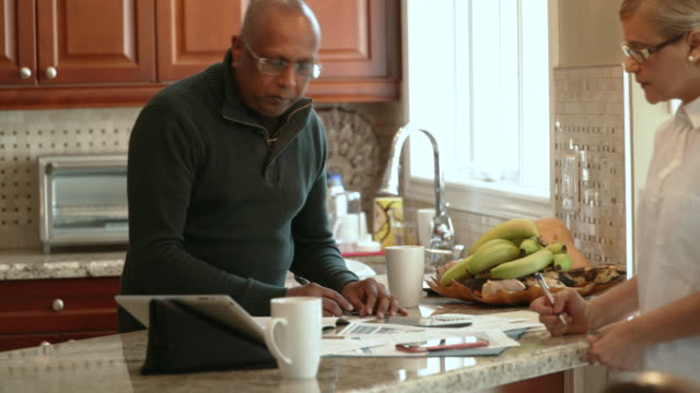 west indian family reviewing family finances in the kitchen - anticipation stock videos & royalty-free footage