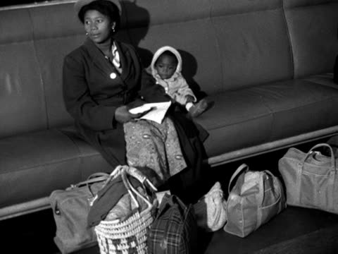 a west indian mother and child wait in the arrivals lounge at southampton docks - southampton hampshire stock-videos und b-roll-filmmaterial