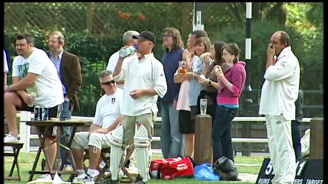 Twickenham EXT Various shots of amateur cricket match in progress on village green Vox pops local people SOT