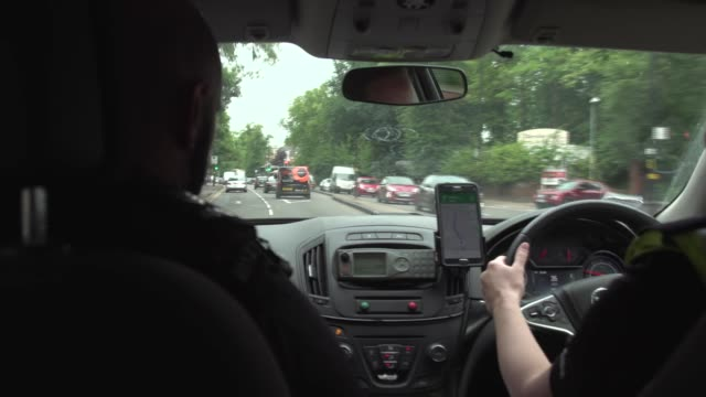 West Midlands Police officers on duty July 2018 West Midlands Police officers in police car chatting and driving through traffic on roads and...