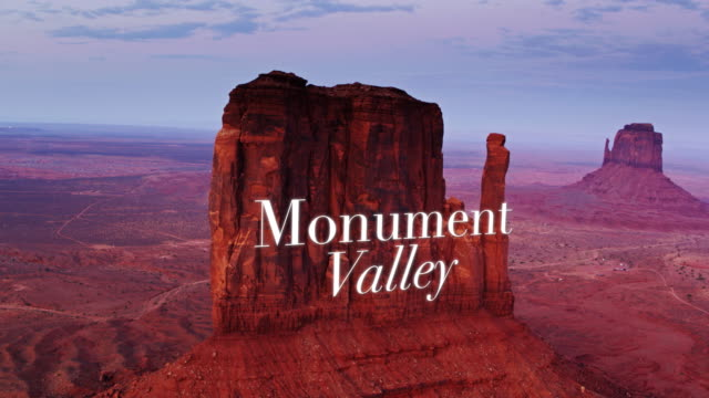 "west mitten butte at sunset with floating text: ""monument valley"" - drone shot - navajo reservation stock videos and b-roll footage"