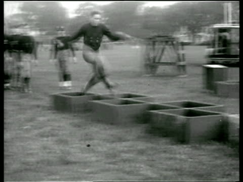 B/W 1929 PAN West Point football player running thru boxes on ground in practice / newsreel