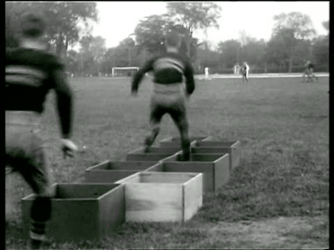 west point football players running thru boxes on ground in practice / newsreel - ウェストポイント点の映像素材/bロール