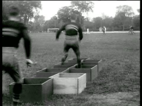 vídeos de stock, filmes e b-roll de west point football players running thru boxes on ground in practice / newsreel - liga esportiva
