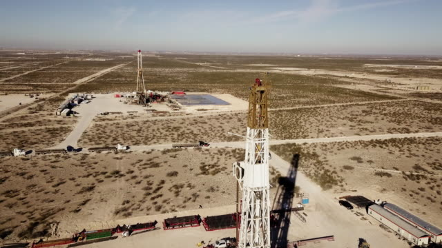 stockvideo's en b-roll-footage met west texas delaware river basin fracking drilling rig at dusk, drone shot - texas