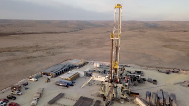 west texas delaware river basin fracking drilling rig at dusk, drone shot - petrol tank stock videos and b-roll footage