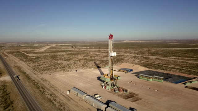 West Texas Delaware River Basin Fracking Drilling rig At Dusk, Drone Shot