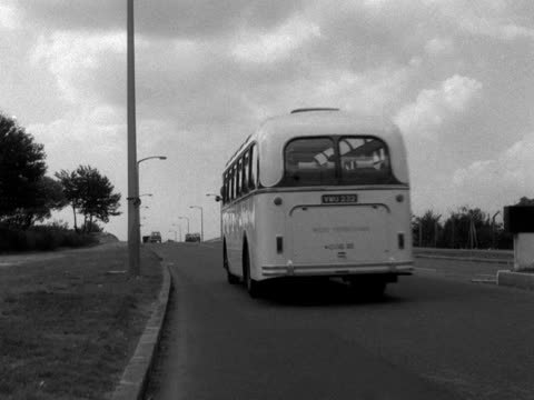 a west yorkshire coach drives away from the camera and along a main road with light traffic - west yorkshire stock-videos und b-roll-filmmaterial