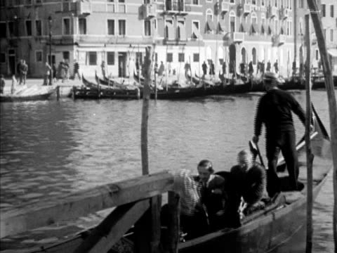 VENICE ITALY Westbrook Van Voorhis w/ same unidentified man both getting into gondola sitting riding boat VS Buildings along canal MS Gondolier WS...