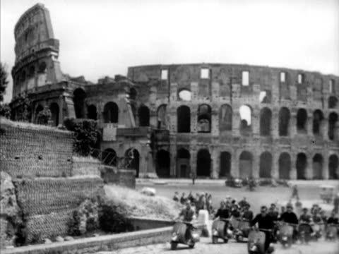ROME ITALY Westbrook Van Voorhis w/ unidentified couple on top of Colosseum couple turning pointing left WS Large group of university students riding...