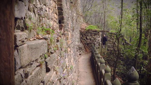 western kung fu disciple wandering through ancient ruins in the wudang shan mountains. - apostel bildbanksvideor och videomaterial från bakom kulisserna