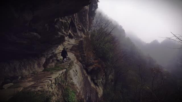 western kung fu disciple wandering through ancient ruins in the wudang shan mountains. - カンフー点の映像素材/bロール
