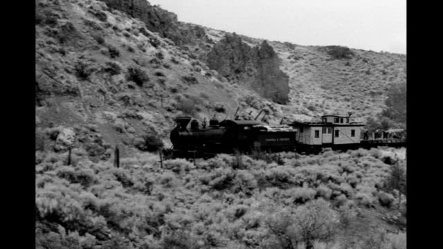 Western scene sagebrush desert camera pans to follow small Virginia and Truckee railroad train passing Western scene with steam engine on January 01...