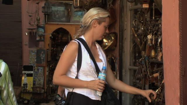vídeos de stock, filmes e b-roll de ms western shoppers looking at antiques, marrakech, morocco - antiquário loja