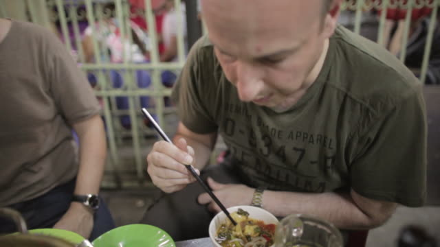 cu western tourist eats food with chopsticks at street restaurant in ho chi minh / ho chi minh city, vietnam - schmecken stock-videos und b-roll-filmmaterial