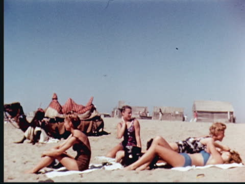vídeos de stock, filmes e b-roll de 1960 montage western tourist women in skimpy bathing suits + bikinis running from beach into ocean waves while pakistani men watch with camel/women sunbathing and climbing on camel/cu women smiling/two pairs of women riding on camels + laughing / pakistan - 1960