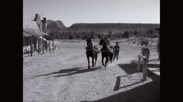 ws pan western town, man running with horses / united states - hängslen bildbanksvideor och videomaterial från bakom kulisserna