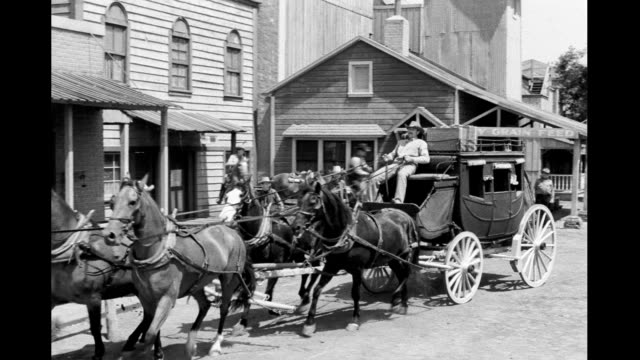 vidéos et rushes de western town with horses wagons men and women pass by / stagecoach rushes into town stops at stage depot small western town on july 25 1950 - animaux au travail