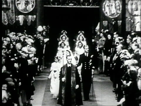 westminster abbey choir singing / the marriage certificate / elizabeth and philip marching down the wedding aisle / congregation of wedding guests... - anno 1947 video stock e b–roll