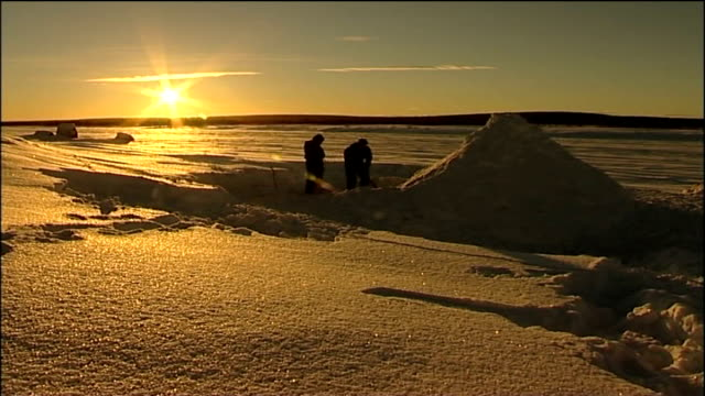 day two two people digging mound of snow with sun setting beyond mp's knelt shovelling snow inside igloo cavity - igloo stock videos & royalty-free footage