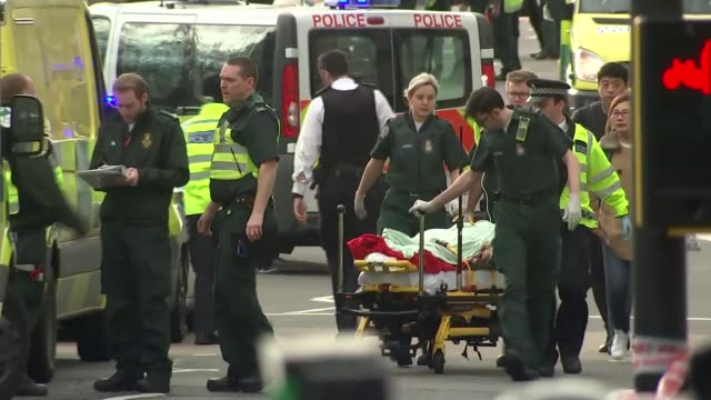 fourth victim named / Prince Charles visits injured in hospital 2232017 Westminster Ambulance crew wheel stretcher along road Ambulances and police...