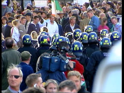 stockvideo's en b-roll-footage met prohunt protestors gathered outside parliament as smoke drifts across tbv riot police along cms man wearing tshirt portraying prime minister tony... - bewegingsbeperkende middelen