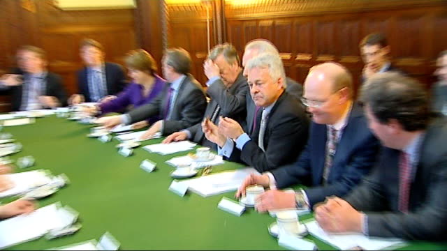 int alan duncan sitting with others at conservative shadow cabinet meeting zoom in as he eats a biscuit - alan duncan stock-videos und b-roll-filmmaterial