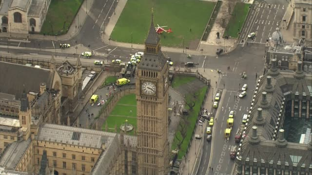 five dead and at least 40 injured air view big ben clock tower with car on pavement and emergency services at scene ambulances and other vehicles... - westminster bridge stock-videos und b-roll-filmmaterial