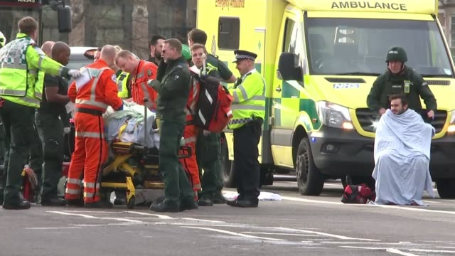 five dead and at least 40 injured injured people being treated by paramedics on westminster bridge - westminster bridge stock-videos und b-roll-filmmaterial
