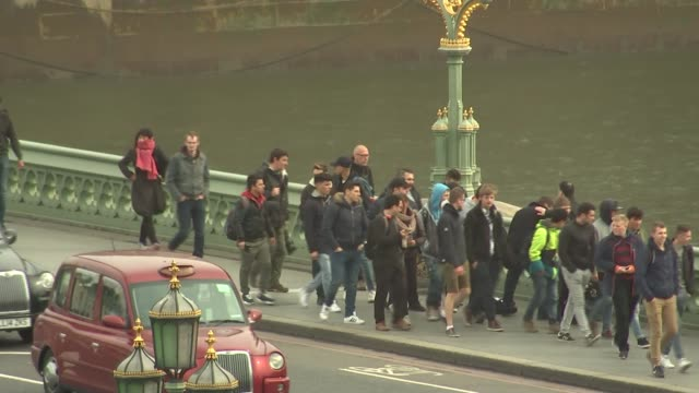 Khalid Masood named as attacker / police investigation Various of pedestrians walking over reopened Westminster Bridge Red London bus across...