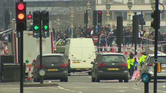 london carries on cordonedoff whitehall pavement with westminster underground statioin in distance long shot of pedestrians over westminster bridge... - house of commons stock videos and b-roll footage