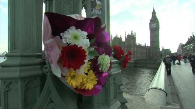 london carries on england london westminster houses of parliament and big ben with westminster bridge in foreground bunch of flowers on bridge... - westminster bridge stock-videos und b-roll-filmmaterial