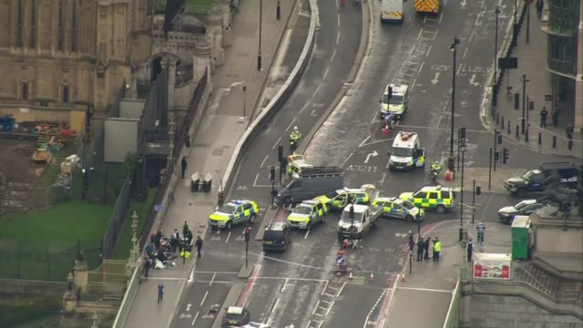 security tightened air view police and injured beside westminster bridge in aftermath of terror attack and concrete barrier separating houses of... - westminster bridge stock-videos und b-roll-filmmaterial