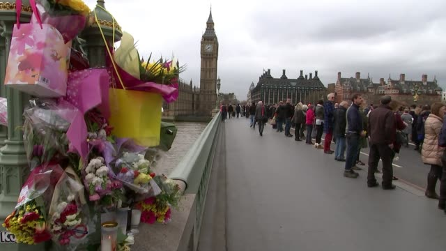 vigil held on westminster bridge one week on westminster close shot flowers tied to westminster bridge with big ben in background and people lined up... - westminster bridge stock-videos und b-roll-filmmaterial