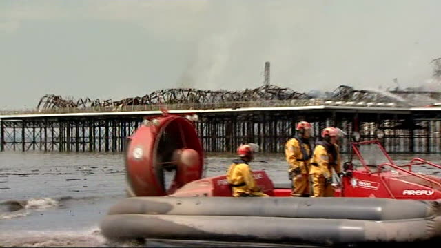 vídeos y material grabado en eventos de stock de weston super mare pier destroyed by fire; fire and rescue team hovercraft along on beach firefighter looking out from pier as water being sprayed on... - vehículo anfibio
