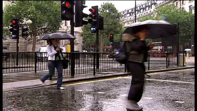wet and windy conditions in london england london ext deck chairs being blown about in the wind in london park woman trying to open umbrella in the... - 2007 stock-videos und b-roll-filmmaterial