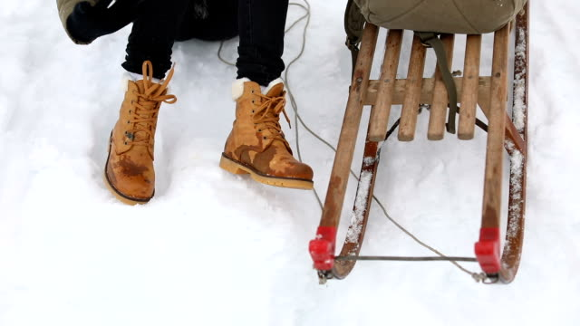 Wet boots and sleigh on the snow