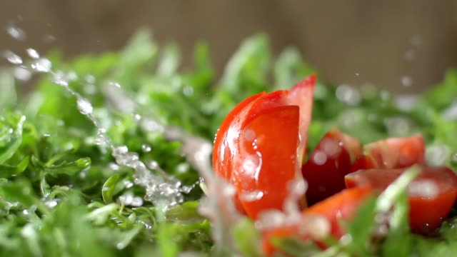 slo mo wet chopped tomato falls on arugula - chopped food stock videos and b-roll footage