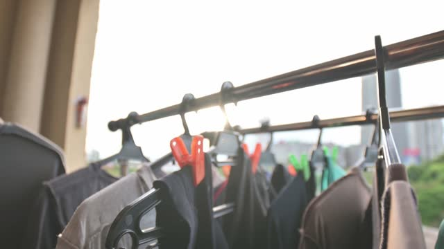 朝のバルコニーにぶら下がっている濡れた布の物干しの服を - ハンガー点の映像素材/bロール