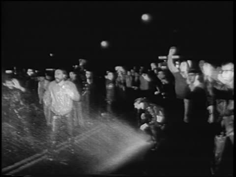 b/w 1967 wet demonstrators cheering at antiwar rally at night / rome italy / newsreel - anno 1967 video stock e b–roll