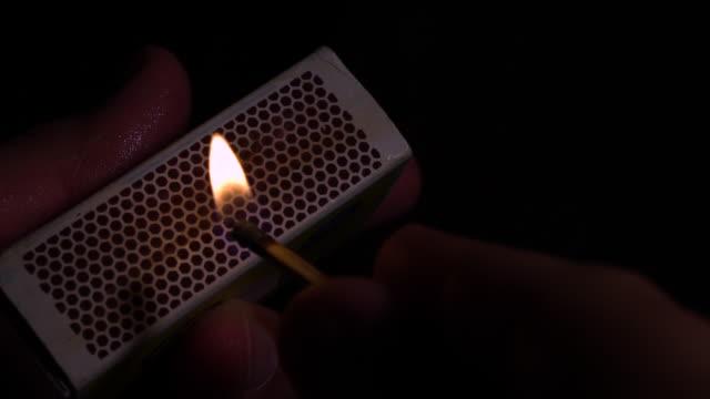 vídeos de stock e filmes b-roll de wet fingers striking a match, slow motion - caixa de fósforos