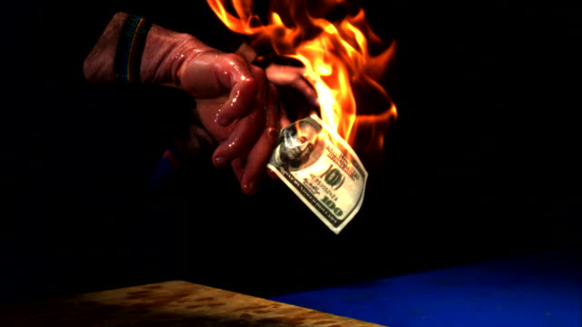 a wet hand waves a flaming hundred-dollar bill. - flammable stock videos & royalty-free footage