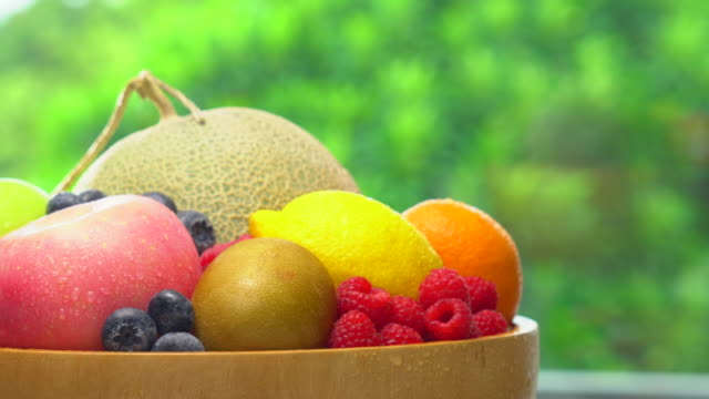 wet mix fruit in wooden bowl rotating on blur lush foliage background - fruit bowl stock videos & royalty-free footage