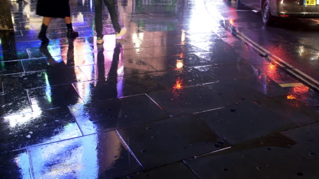 wet pavement reflecting city lights - asfalto video stock e b–roll