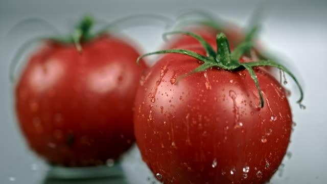 stockvideo's en b-roll-footage met slo mo cu natte tomaat vallen op een tafel - kleine groep dingen