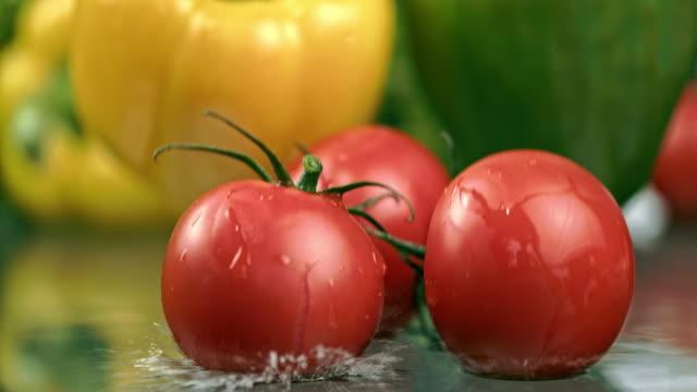 SLO MO natte tomaten en paprika vallen op een tafel