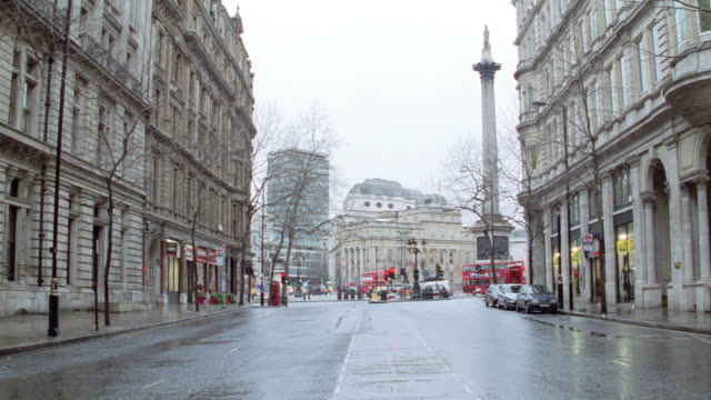 a wet, vacant city street leads to trafalgar square in the heart of london. - 2003 stock videos & royalty-free footage