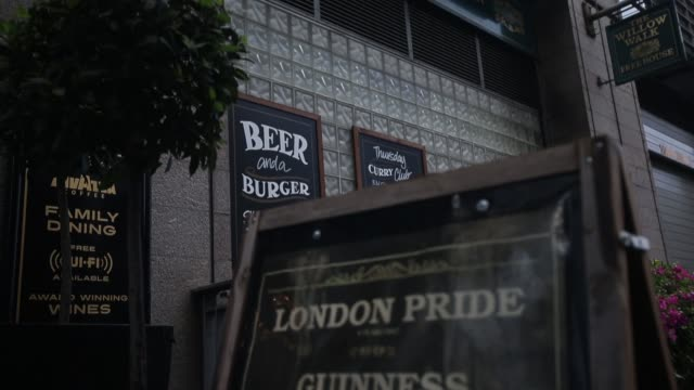 wetherspoon plc employees walk behind the bar at one of the company's pubs in london, u.k., on friday, sept. 13 pull focus from credit card reader to... - lager stock videos & royalty-free footage
